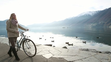 Young woman walking with bicycle by the lake