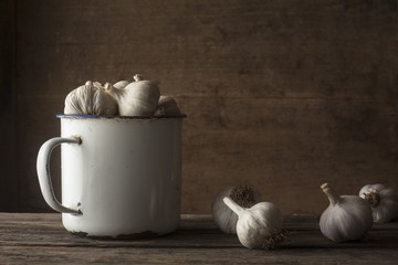 garlic with vintage iron mug over wooden surface