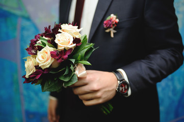 Groom in a classic costume holding a beautiful wedding bouquet