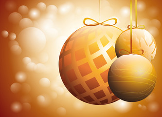three golden christmas baubles over glowing warm background