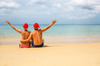couple in red Santa hats at tropical beach