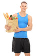Young athlete holding a bag full of groceries