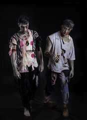 Two male zombies standing on black background