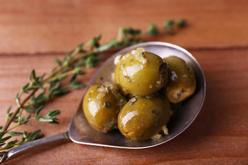 Green olives in oil with spices and rosemary in spoon