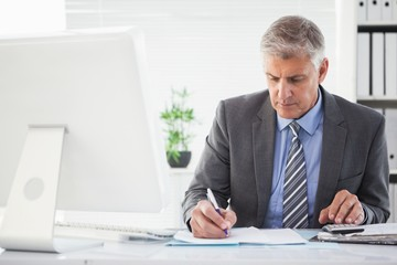 Focused businessman writing something down