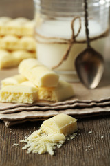 Tasty white porous chocolate and glass of milk,