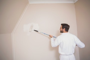 Painter painting the walls white