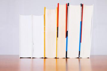 Libri in fila su piano riflettente