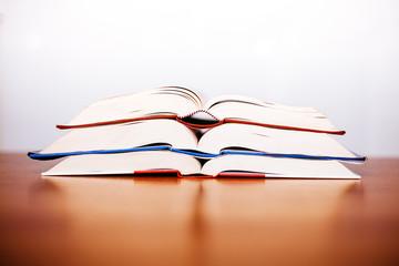 Pila di libri aperti su tavolo di legno