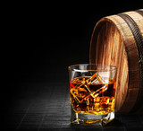 Glass of cognac on the vintage wooden barrel