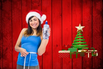 Fit brunette measuring her waist and holding bottle