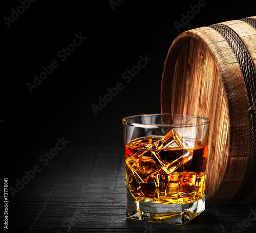 Poster Alcohol Glass of cognac on the vintage wooden barrel