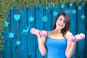 Composite image of smiling fit brunette holding dumbbells