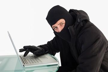 Burglar using laptop while looking at camera