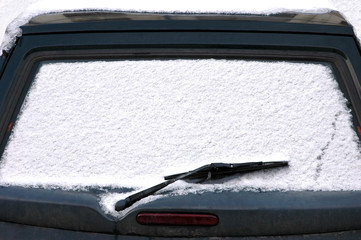 Car windshield covered with snow