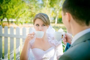 bride and groom sitting at a table in a cafe and drink coffee