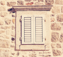 retro window with wooden shutters and stone walls