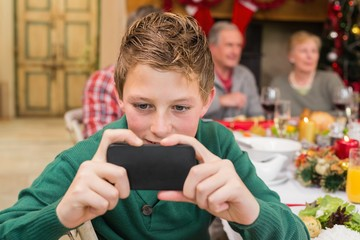 Young boy holding smartphone during christmas dinner