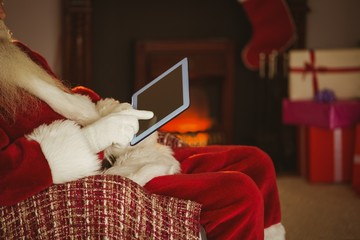 Mid section of santa touching tablet