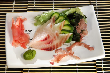 Sushi menu: shrimp with slices of cucumber, seaweed on a plate.