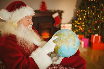 Santa claus pointing his finger on the globe