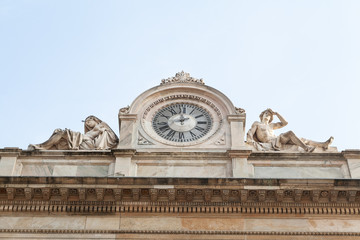 Antique facade with clock and naked sculptures