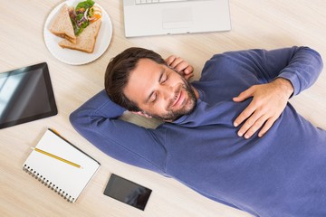 Happy man lying on floor surrounded by his things