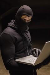 Burglar standing holding laptop while looking at camera