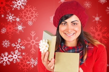 Composite image of smiling brunette opening christmas gift