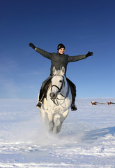 Funny girl riding on white horse sunny winter