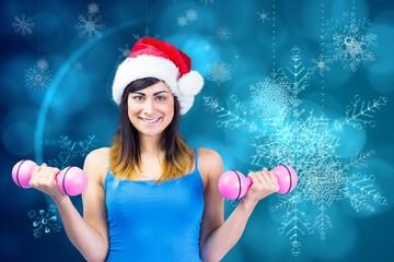 Composite image of festive fit brunette holding dumbbells