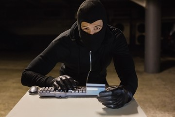 Burglar shopping online with laptop