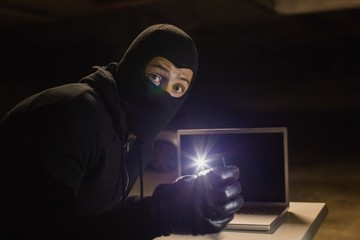 Robber looking at camera while making light with his phone