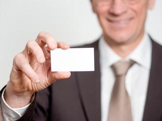 Geschäftsmann hält Visitenkarte hoch