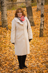 Elegant middle-aged woman in the autumn park
