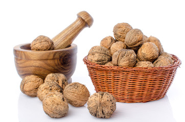 Walnuts in a basket and a wooden mortar