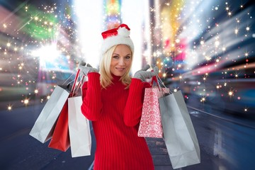 Composite image of happy festive blonde with shopping bags