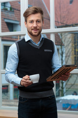 junger Geschäftsmann mit Kaffee und Tablet