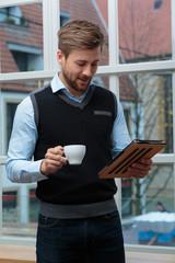 junger Geschäftsmann mit Kaffee schaut auf Tablet