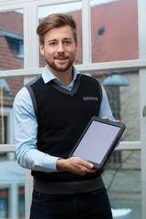 junger Geschäftsmann präsentiert Tablet lachend