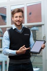 junger Geschäftsmann zeigt auf Tablet freudig erregt