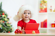 toddler girl in christmas hat with tablet pc