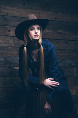 Cowgirl jeans fashion woman with long blonde hair. Sitting on wo