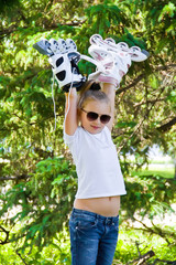 Cute girl playing with roll skates