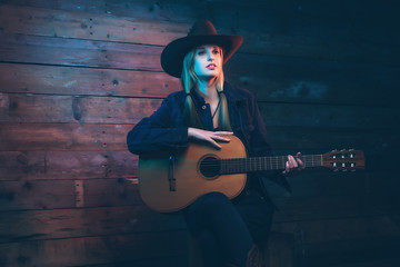Cowgirl country singer with acoustic guitar. Wearing blue jeans