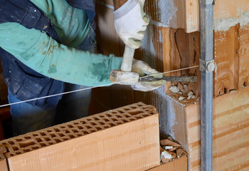 Worker with chisel on an internal wall in hollow blocks of brick
