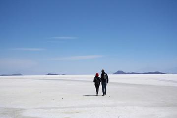Tourists walk in a salt desert of Salar de Uyuni, Bolivia