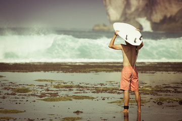 Man surfer with surfboard on a coastline