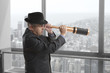 Businessman looks through a telescope