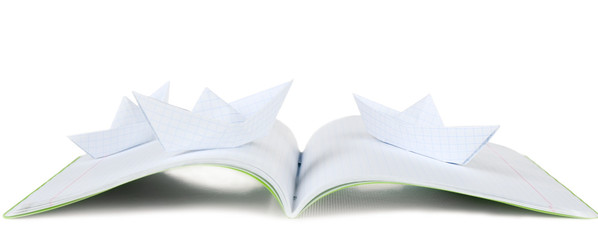 Origami boats on notebook, isolated on white